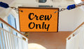 Crew only sign a hanging over a stairway that says secured by a rope Stock Photography