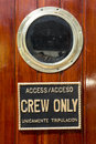 Crew only sign on wooden door with brass porthole window Royalty Free Stock Photos
