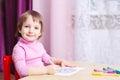 A criança de sorriso tira uma imagem por marcadores coloridos Fotografia de Stock Royalty Free