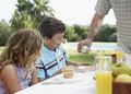 Crianças colhidas de pouring syrup by do pai Fotos de Stock Royalty Free