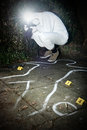 Crime scene photographer taking a photo fo during the forensics research of a murder in a park Royalty Free Stock Image