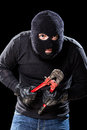 Criminal a burglar wearing a balaclava holding huge wire cutters over black background Royalty Free Stock Photography