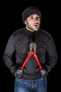 Criminal a burglar wearing black clothes holding huge wire cutters over black background Royalty Free Stock Image
