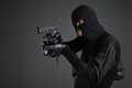 Criminal side view of man in black balaclava aiming with a gun and flashlight while standing isolated on black Stock Photo