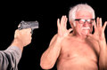 Criminal theratening scared old man with a gun naked Stock Photography