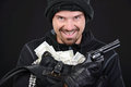 Criminality burglar with stolen goods angry burglar holding stolen goods while smiling against black background Stock Photography
