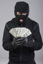 Criminality robber in a mask rejoice stolen money gray background Stock Images