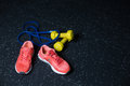 Crimson bright sneakers, yellow vivid dumbbells, blue expander, equipment for a workout on a dark blurred background. Royalty Free Stock Photo