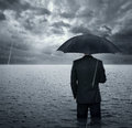 Crisis businessman standing in the dramatic ocean before storm Royalty Free Stock Images