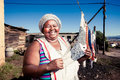 Crisp and clean plump african woman proudly showing off her washing in the township Stock Image