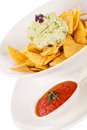 Crisp corn nachos with guacamole sauce spicy fresh and a topping of avocado served as a snack or appetizer in a white bowl Stock Images