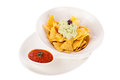 Crisp corn nachos with guacamole sauce spicy fresh and a topping of avocado served as a snack or appetizer in a white bowl Stock Image