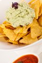 Crisp corn nachos with guacamole sauce spicy fresh and a topping of avocado served as a snack or appetizer in a white bowl Stock Photos