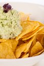 Crisp corn nachos with guacamole sauce spicy fresh and a topping of avocado served as a snack or appetizer in a white bowl Royalty Free Stock Photo