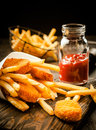 Crisp golden battered fried fish with chips portions served potato in a paper cone a bottle of tomato ketchup in a rustic Stock Photography