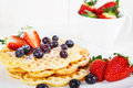 Crisp golden fresh baked waffle topped with strawberries and blueberry blueberries on white table Stock Images