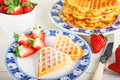 Crisp golden fresh baked waffle topped with strawberries on whit white table Royalty Free Stock Photo