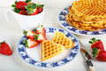 Crisp golden fresh baked waffle topped with strawberries on whit white table Stock Photography