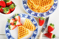 Crisp golden fresh baked waffle topped with strawberries on whit white table Stock Image