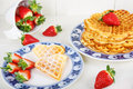 Crisp golden fresh baked waffle topped with strawberries on whit white table Royalty Free Stock Photos
