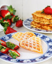 Crisp golden fresh baked waffle topped with strawberries on whit white table Stock Photo