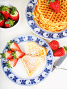 Crisp golden fresh baked waffle topped with strawberries on whit white table Stock Photos