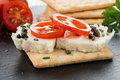 Crispbread with fromage tomato and olives on black ardoise tray Stock Photography