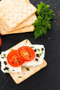 Crispbread with fromage tomato and olives on black ardoise tray Stock Photo