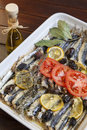 Crispy baked fresh sardines mackerel fishes mediterranean with organic tomato laurel rosemary and tasty olives selective focus Stock Photography