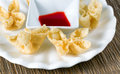 Crispy fried wanton and sauce in white bowl on bamboo mat Royalty Free Stock Photo