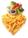 Crispy golden crinkle cut french fries arranged in a heart shape symbolic of love romance or valentines day with with dips Stock Images