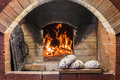 Crispy loaf of bread lying on the edge of the Russian stove on the hearth Royalty Free Stock Photo