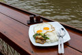 Crispy pork stir fried with kale and twin eggs at riverside Royalty Free Stock Photography