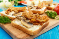Crispy toasted white bread in the shape of a square with mushrooms, onions, french fries, tartar sauce on a cutting board