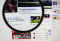 Cristiano ronaldo photo of ronaldos official facebook page on a monitor screen through a magnifying glass Stock Photography
