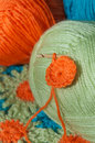 Crochet craft cute project with three bright and colourful balls of yarn green blue orange and hook Royalty Free Stock Photos