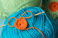 Crochet fun cute project with three bright and colourful balls of yarn green blue orange and hook Stock Photos