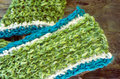Crochet scarf bright green and blue fluffy and warm in half double stich against wooden background Royalty Free Stock Photography
