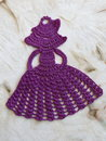 Crochet violet woman on old fabric Stock Photo