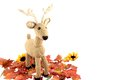Crocheted deer with autumn leaves a handcrafted crochet on a white background surrounded by Royalty Free Stock Photo