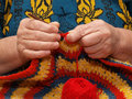 Crocheting hands of the elderly woman knitting by means of a hook Stock Image