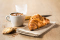 Croissant breakfast capuccino and delicious cookies on a wooden table Royalty Free Stock Photo