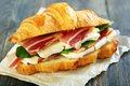 Croissant with ham and brie cheese on white parchment Stock Photo