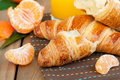 Croissant and mandarine close up of fresh tangerine for breakfast on wooden table horizontal Royalty Free Stock Photos