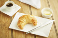 Croissant pastry on white dish and wooden table top Stock Images
