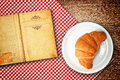 Croissant recipe croisant on a plate and old open book with copys pace for your text Royalty Free Stock Photo