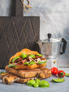 Croissant sandwich with smoked meat prosciutto di parma sun dried tomatoes fresh spinach and basil on stone textured grey Royalty Free Stock Images