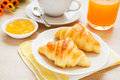 Croissants coffee cup and juice on wooden table a Royalty Free Stock Photography