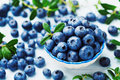 Crop of blueberry or great bilberry in bowl on blue wooden table. Organic superfood and healthy nutrition. Royalty Free Stock Photo