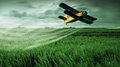 A crop dusting plane working over a field Royalty Free Stock Photo